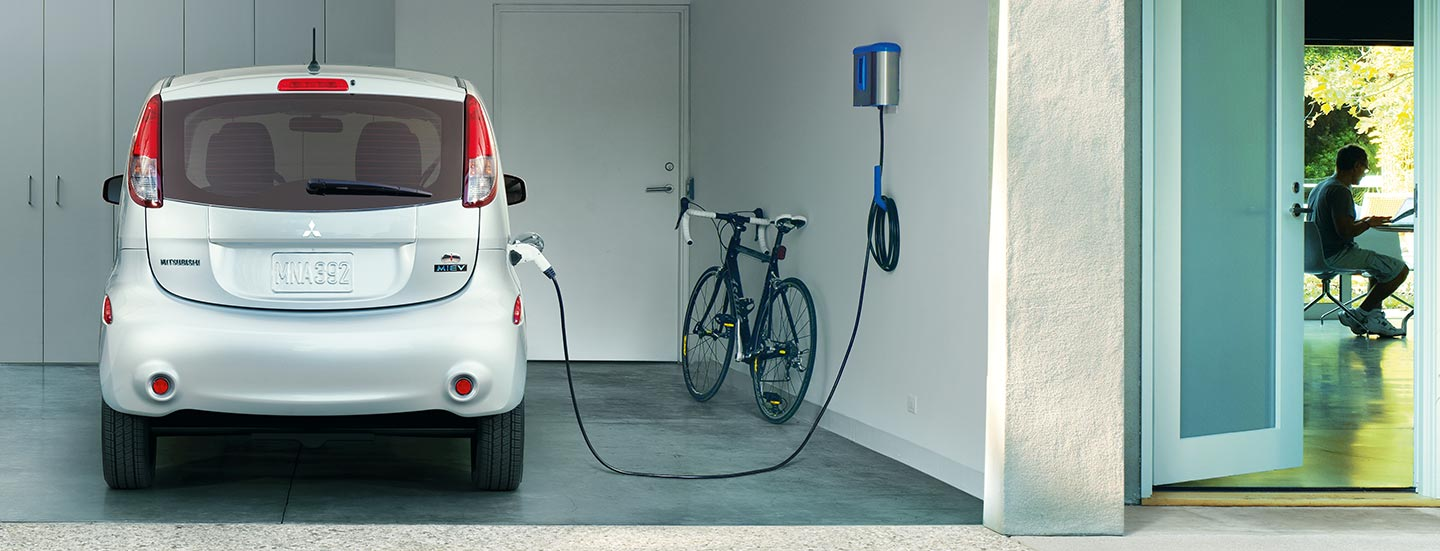 2017 Mitsubishi i-MiEV fully electric car plugged into home charger in car garage
